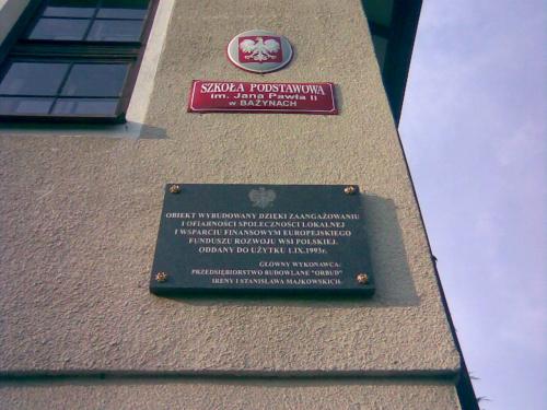 Bażyny k. Ornety - tablica pamiątkowa na ścianie budynku szkoły