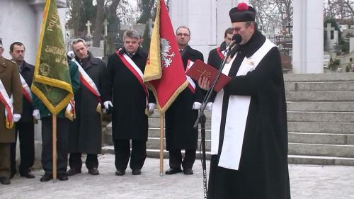 Ks. kan. dr Andrzej Panasiuk na tle pomnika ks. Piotra Wawrzyniaka w przepięknej modlitwie za zmarłych i poległych Powstańców Wielkopolskich